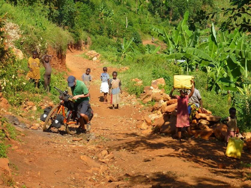 Johan lopend met fiets over stoffig zandpad met Oegandese kinderen