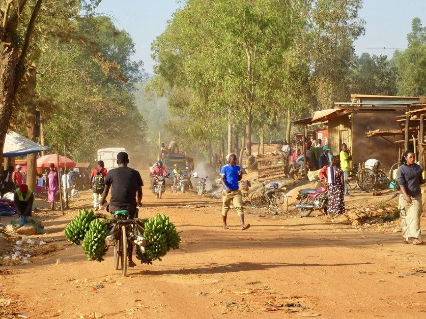 Stoffige zandweg met mensen en huisjes in Oeganda