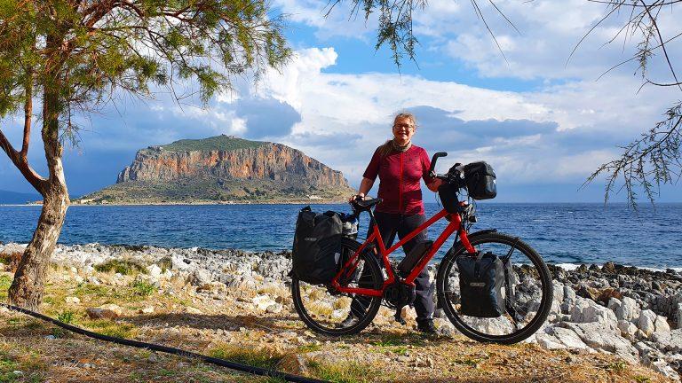 Op de voorgrond: Carla met fiets aan het water. Op de achtergrond: Grieks eiland, aan de andere kant van het water.