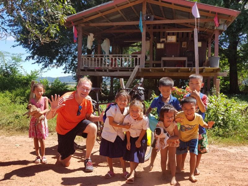 Winkeleigenaar Eric in Laos, vergezeld met met kinderen tijdens zjn fietstocht langs de Mekong. Die tocht ging door Thailand, Laos, Cambodja en Vietnam.