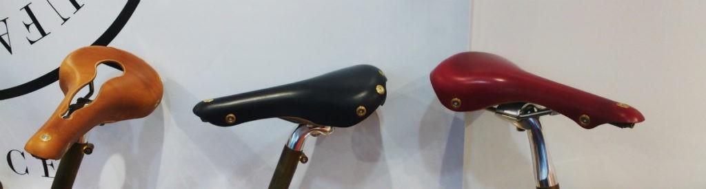 Drie lederen fietszadels van Gilles Berthoud,: bruin, zwart en rood