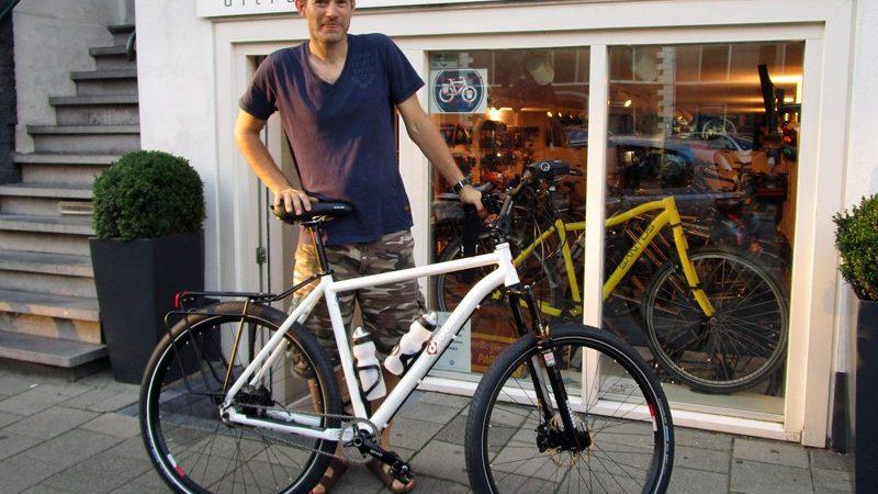 Arjen met een fiets waar wij erg enthousiast over waren, maar die eigenlijk net niet paste in ons assortiment, want het is meer een mountainbike. De idworx RocknRohler.