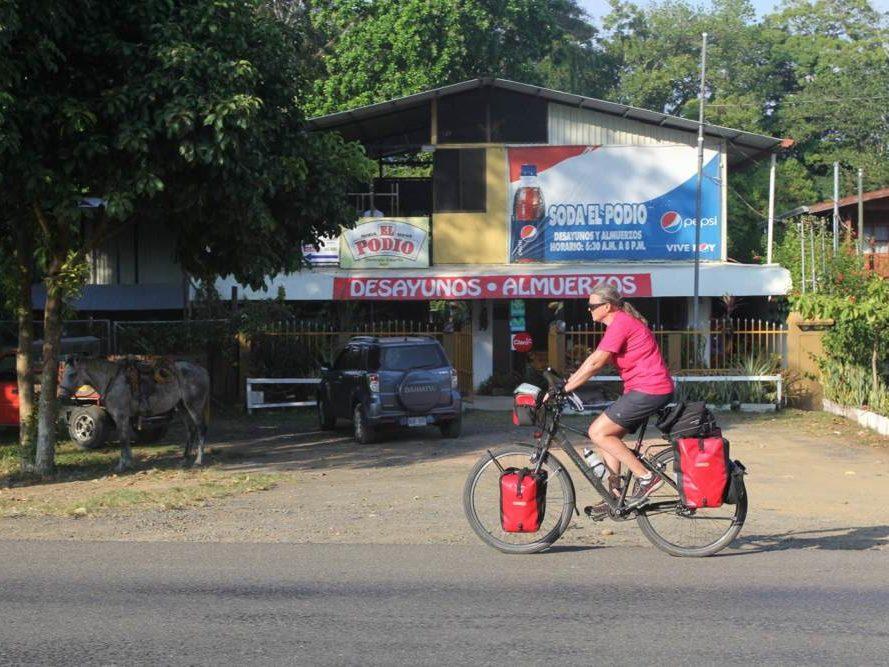 Carla op vakantiefiets op asfaltweg en winkeltje op Costa Rica