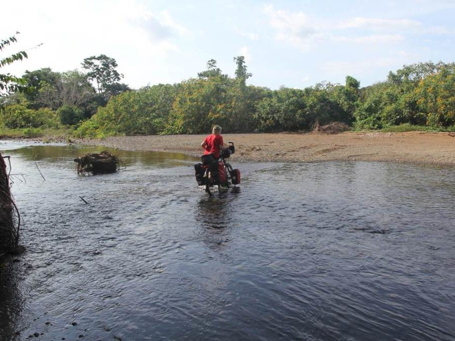 Carla met fiets door water op Costa Rica