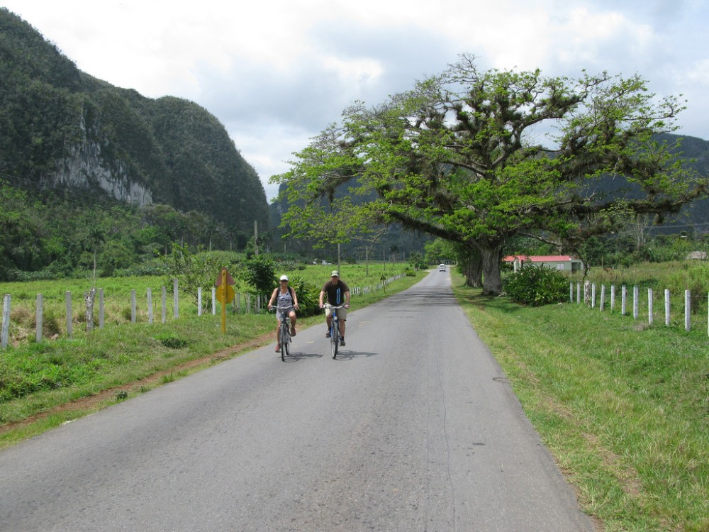 Twee fietsers op asfaltweg in de natuur op Cuba