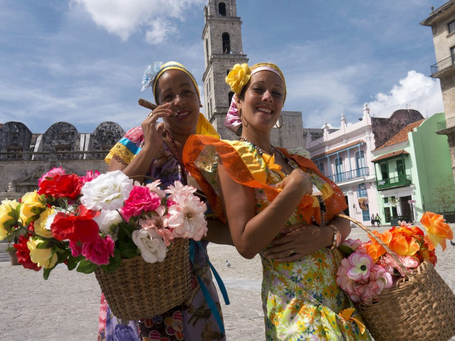 Twee Cubaanse dames met bloemenmanden in kleurrijke kleding