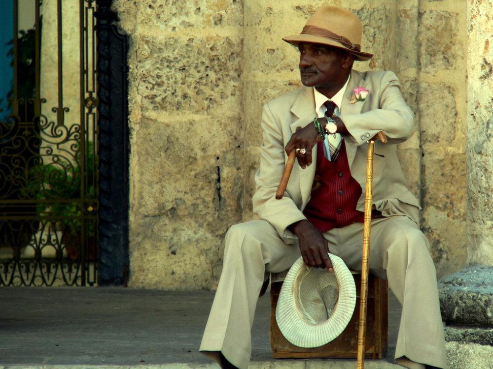Cubaanse man zittend op een koffertje op Cuba