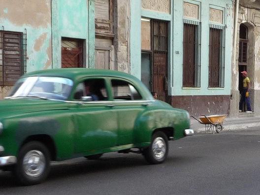 Groene auto op straat op Cuba