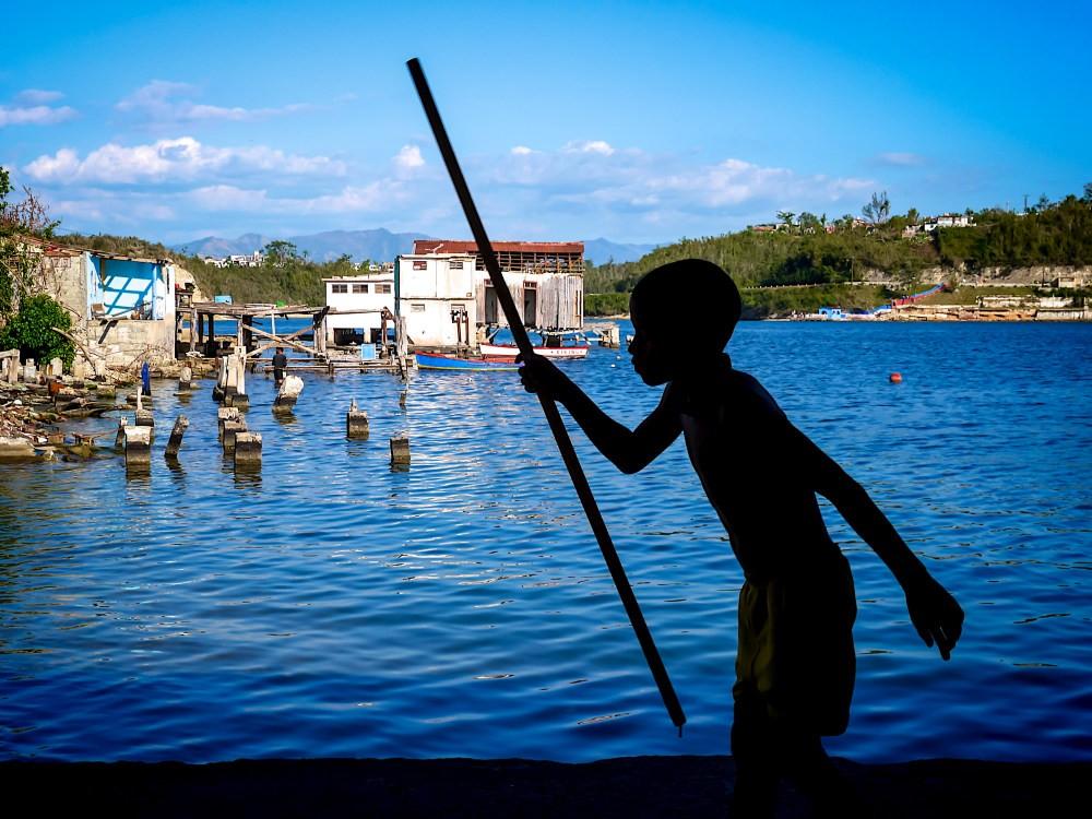 Jongen met stok bij water op Cuba