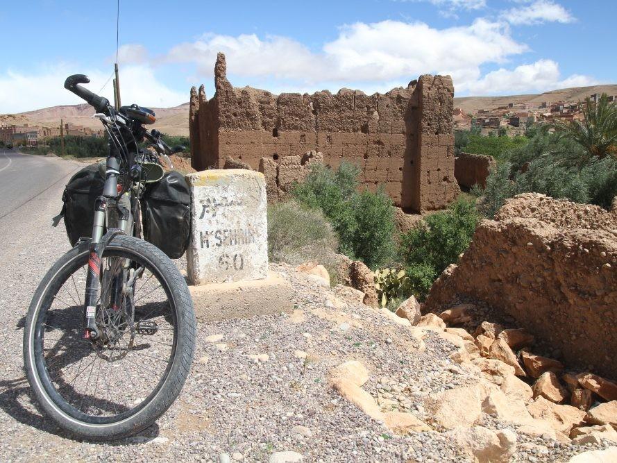 Vakantiefiets tegen wegwijzer langs de weg in Marokko