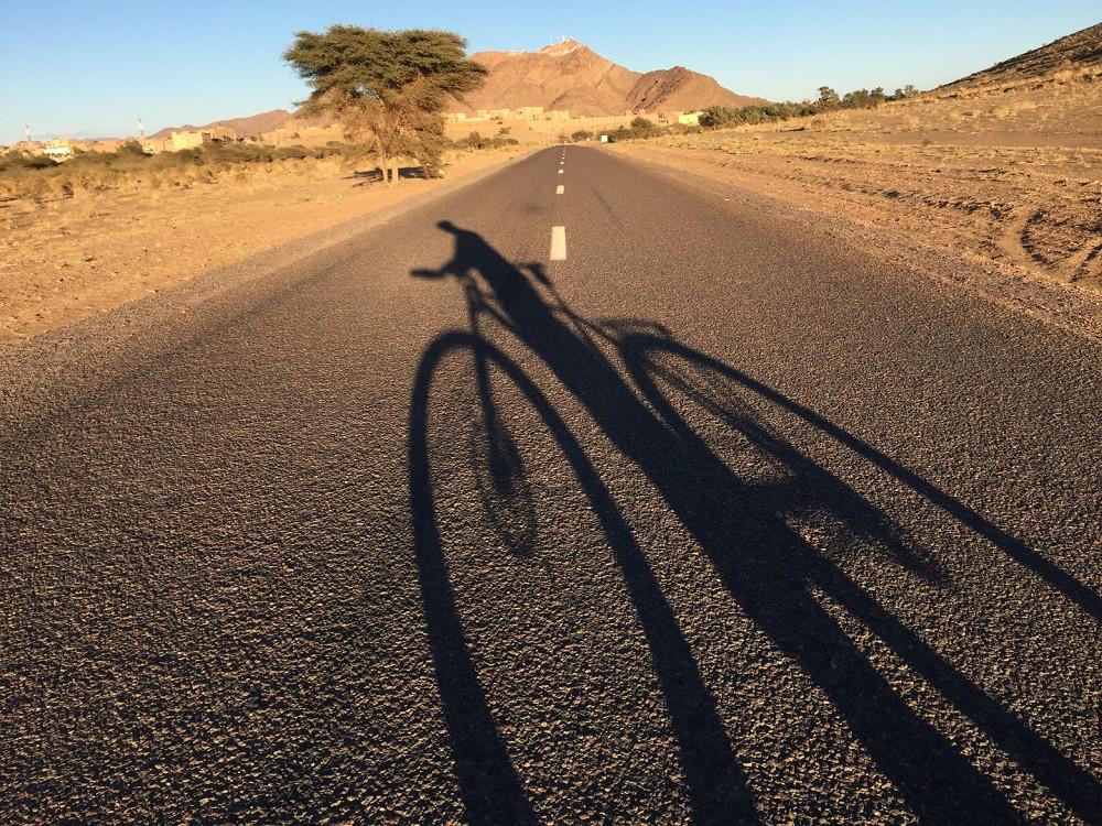 Schaduw van een fiets op asfaltweg in Marokko