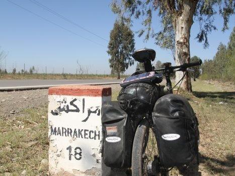 Bepakte vakantiefiets bij wegwijzer met Marrakech erop in Marokko