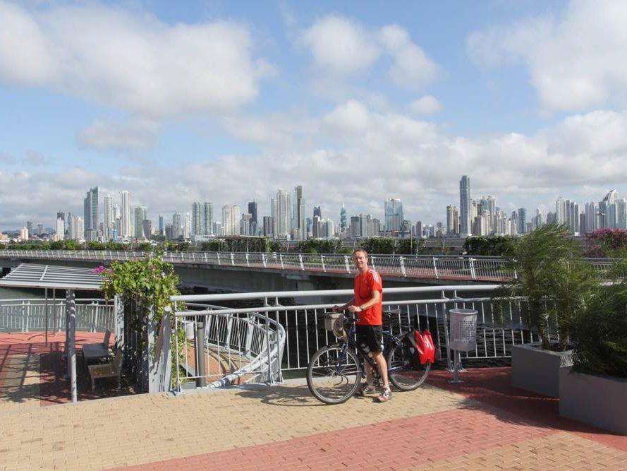 Eric met fiets voor uitzicht op Panama Stad in Panama