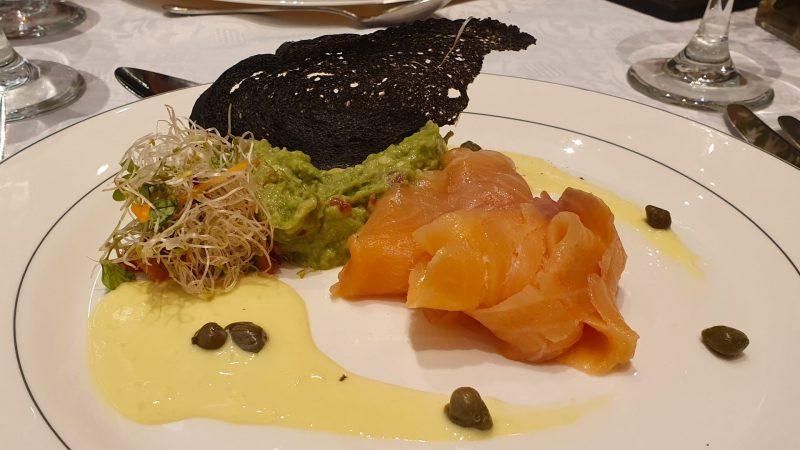 Lekker eten in Salta, Argentinie, zalm met guacemole, olijfpoeder, sepiabrood, remouladesaus en radijscarpaccio